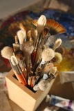 Brushes for painting in a wooden glass on a backgr. It is a lot of brushes for painting in a wooden glass on a background a palette Stock Photography