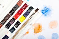 Brushes, paints and drawings on paper on blue background Stock Images