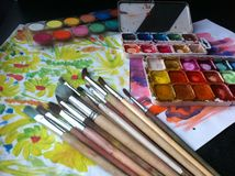 Brushes, paints, drawings on the table. Brushes and paints for creativity, drawing on a table, hobby stock photography