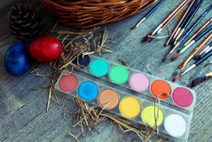 Brushes, paints and easter eggs on the tableb. Brushes and paints for coloring eggs for Easter stock image
