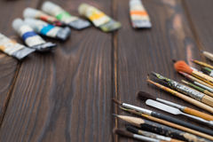 Brushes and paints are spread out on a dark wooden surface Stock Photos