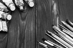 Brushes and paints are spread out on a dark wooden surface Royalty Free Stock Images