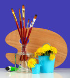 Brushes with the palette and dandelions Stock Photography