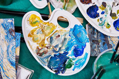Brushes, palette, paint and water on table Stock Photography