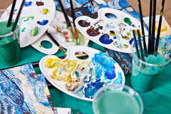 Brushes, palette, paint and water on table Stock Images