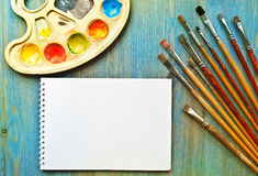 Brushes, palette and sketch pad Stock Photos