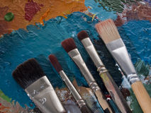 Brushes on a pallet. Five paintbrushes on a color pallet Stock Photos