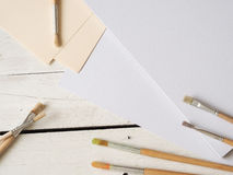 Brushes and paper sheets. Brushes with paper sheets on a wooden background, creativity background Stock Photos