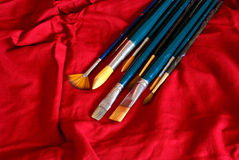 Brushes on red background Stock Photo