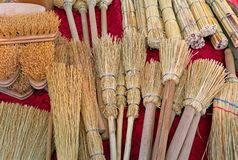 Brushes and small brooms in sorghum at market. Many brushes and small brooms in sorghum for sale on the stand of local market royalty free stock photo