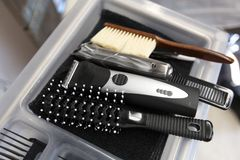 Brushes, trimmers and comb on tray at hair salon. Hair tools, grooming and hairdressing concept - brushes, trimmers and comb on tray at barbershop royalty free stock images