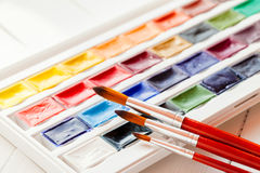 Brushes for water color painting and set of watercolor paints. On table. Selective focus Royalty Free Stock Photo