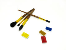 Brushes and watercolor couvettes. On white background in a chaotic manner Stock Photos