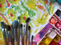 Brushes, watercolor, drawings on the table. Brushes, watercolor, children`s watercolor drawings on a sheet of paper on the table royalty free stock photos