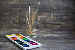 Brushes and watercolor paints. Brushes in vase and watercolor paints on wooden background. Horizontal imagination Royalty Free Stock Images