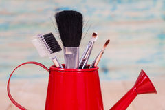 Brushes in watering can Stock Photos