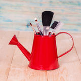 Brushes in watering can Stock Images