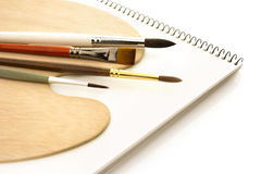 Brushes with wooden palette and sketchbook isolated Stock Photo