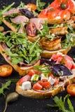 Brushetta为酒设置了 小三明治,蕃茄,帕尔马干酪,新鲜的蓬蒿品种与熏火腿的 图库摄影