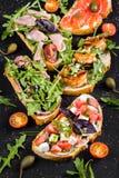 Brushetta为酒设置了 小三明治,蕃茄,帕尔马干酪,新鲜的蓬蒿品种与熏火腿的 免版税库存照片