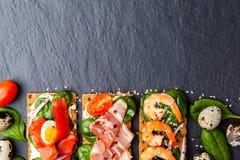 Brushetta που τίθεται στο σκοτεινό υπόβαθρο Ποικιλία των μικρών σάντουιτς δ στοκ εικόνα