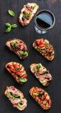 Brushetta установило с стеклом красного вина Малые сандвичи на темной деревянной предпосылке, взгляд сверху Стоковая Фотография RF
