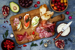 Brushetta or authentic traditional spanish tapas set for lunch table. Sharing antipasti on party picnic time on blue background Stock Photos