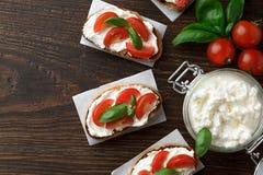 Brushetta crujiente con los tomates, el queso Feta y la albahaca en fondo de madera Imágenes de archivo libres de regalías