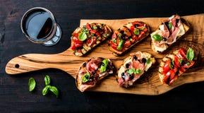 Brushetta fijó y vidrio de vino rojo Pequeños bocadillos con el prosciutto, tomates, queso parmesano, albahaca fresca, balsámica fotografía de archivo