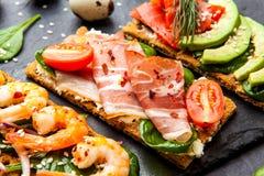 Brushetta a placé sur le fond foncé Variété de petits sandwichs d photographie stock libre de droits