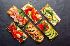 Brushetta a placé sur le fond foncé Variété de petits sandwichs d photos stock