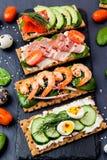 Brushetta a placé sur le fond foncé Variété de petits sandwichs d images stock