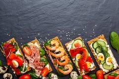 Brushetta a placé sur le fond foncé Variété de petits sandwichs d photographie stock