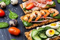 Brushetta a placé sur le fond foncé Variété de petits sandwichs d image stock