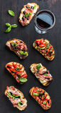 Brushetta set with glass of red wine. Small sandwiches on dark wooden background, top view Royalty Free Stock Photography