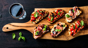 Brushetta set and glass of red wine. Small sandwiches with prosciutto, tomatoes, parmesan cheese, fresh basil, balsamic stock photography