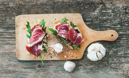 Brushetta set with smoked meat, arugula, garlic and dried tomato Royalty Free Stock Images