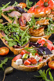Brushetta set for wine. Variety of small sandwiches with prosciutto, tomatoes, parmesan cheese, fresh basil stock photography