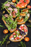 Brushetta set for wine. Variety of small sandwiches with prosciutto, tomatoes, parmesan cheese, fresh basil. And balsamic creme served with glass of red wine on Stock Image