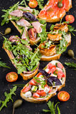 Brushetta set for wine. Variety of small sandwiches with prosciutto, tomatoes, parmesan cheese, fresh basil. And balsamic creme served with glass of red wine on Royalty Free Stock Photo