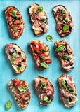 Brushetta set for wine. Variety of small sandwiches on turquoise blue backdrop, top view stock image