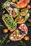 Brushetta stellte für Wein ein Vielzahl von kleinen Sandwichen mit Prosciutto, Tomaten, Parmesankäseparmesankäse, frischer Basili Stockbild
