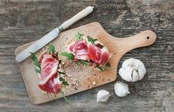 Brushetta uppsättning med rökt kött, arugula, vitlök och den torkade tomaten Arkivfoton