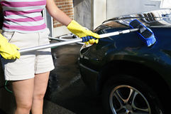 Brushing a car. Woman with a brush washing an SUV car Royalty Free Stock Photography