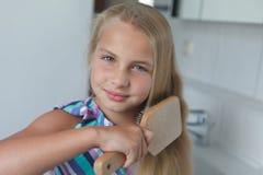 Brushing hairs. Little girl brushing her hairs Stock Photo