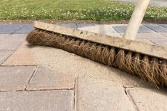Brushing kiln dried sand in to newly laid block paving. Close up of brush brushing kiln dried sand in to joints between newly laid block paving stock photo