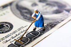 Brushing money. Miniature working woman with a rake or broom on a hundred dollar bill Stock Photography
