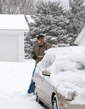 Brushing off snowy car Stock Photography