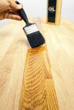 Brushing oil onto a wood surface. Brushing a protective oil treatment onto a solid oak kitchen worktop. Selective focus on foreground wood Stock Photo