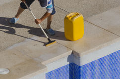 Brushing the poolside. A worker is cleaning a swimming pool brushing the poolside Stock Photography